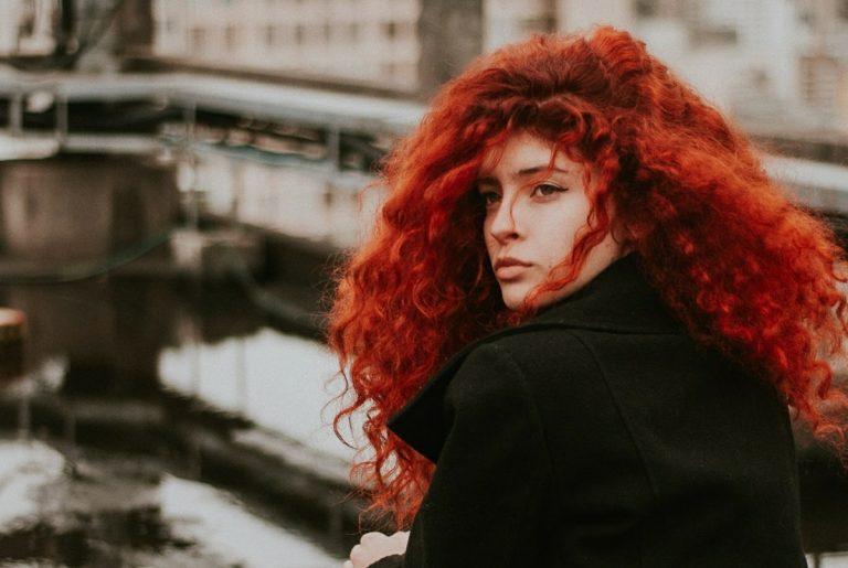foto de cabelo cacheado ruivo longo em postagem sobre cabelo embaraçado com causas e soluções