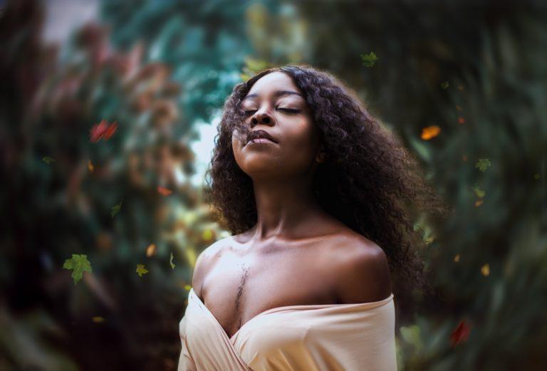 Mulher negra com cabelo longo e crespo ilustra post sobre como escolher produtos para facilitar sua transição capilar
