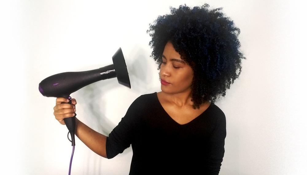 como usar difusor de cachos - foto de mulher com cabelo crespo segurando difusor de cachos