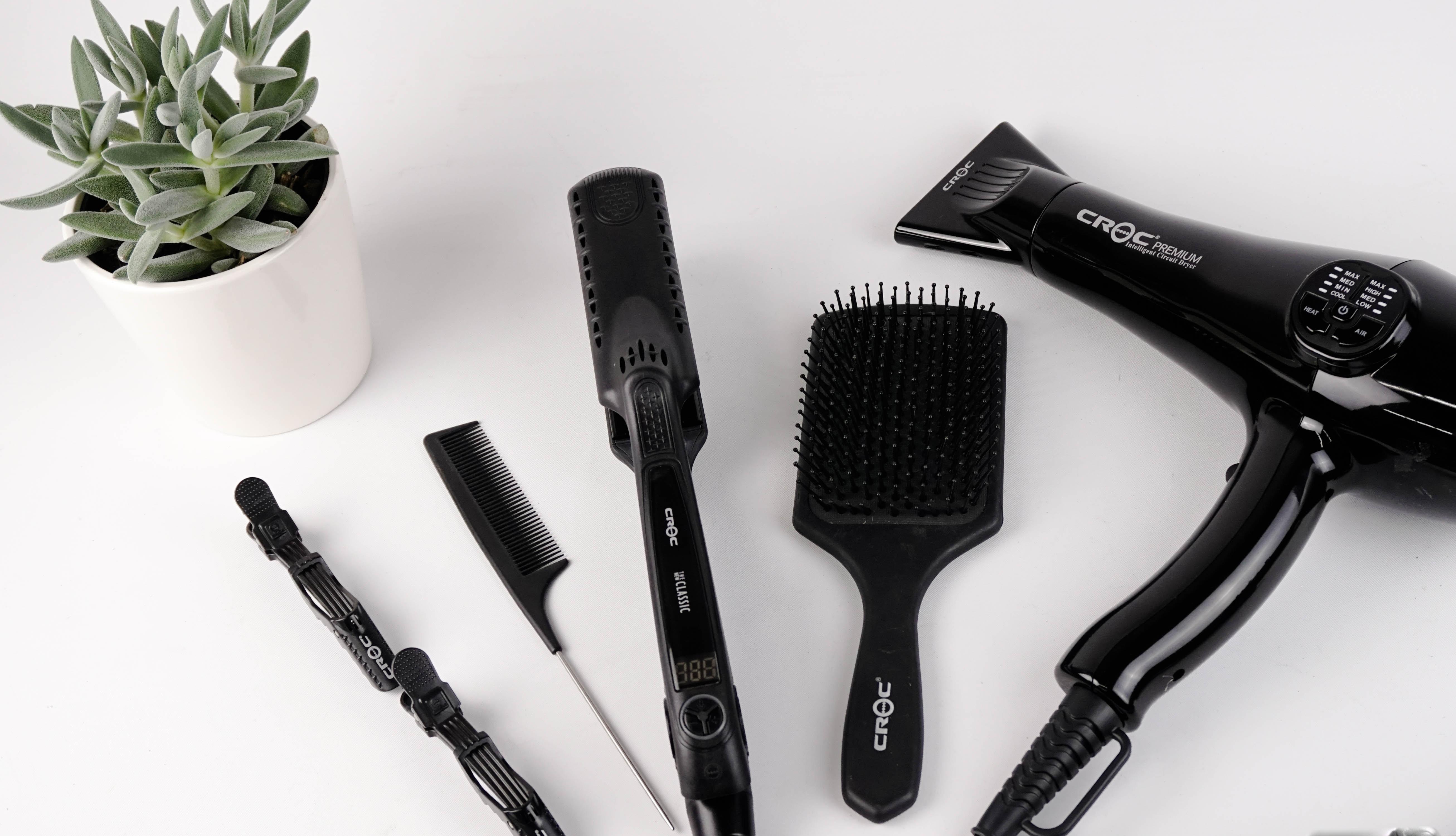 crescimento capilar saudável - 7 dicas essenciais para fazer o cabelo crescer mais rápido de forma segura. A foto possui itens usados para modelar os cabelos como secador, chapinha, escova, pente e babyliss. O texto recomenda a redução de danos externos.