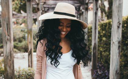 como fazer detox capilar em casa imagem ilustrativa com mulher usando chapéu e sorrindo