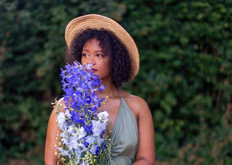 Cabelo crespos e cacheados são mais frágeis que cabelos lisos? imagem de mulher negra com cabelo natural e flores nas mãos