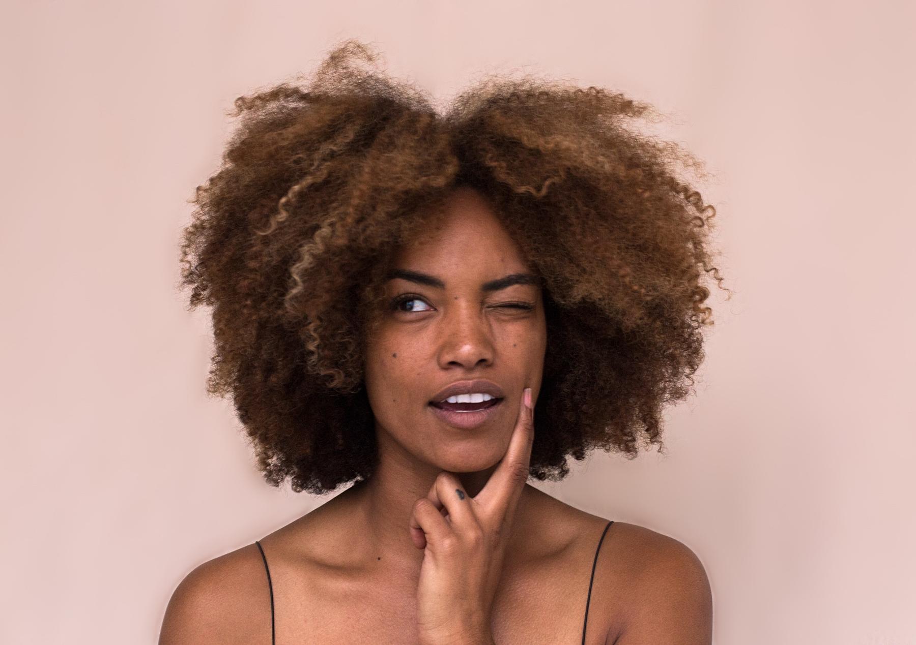 imagem de mulher negra de cabelos crespos com expressão de interrogação. texto sobre ácido hialurônico para cabelos crespos e cacheados: vantagens e dicas