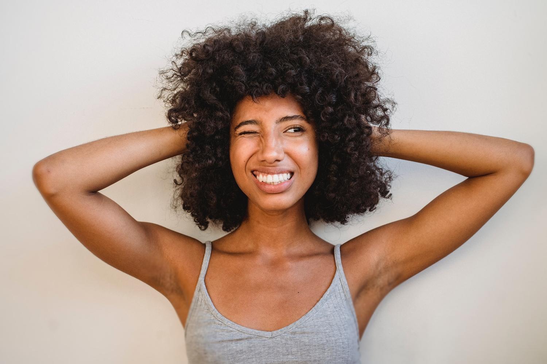 imagem ilustrativa,mulher de cabelos cacheados com expressão preocupada. texto sobre receitas caseiras para caspa