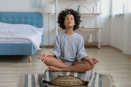 transição capilar infantil. foto ilustra menina de cabelo crespo em pose de concentração, imagem ilustrativa para abordar o tema crianças em transição capilar
